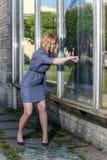 非常恼怒的由她的拳头的妇女刹车的玻璃窗 免版税库存图片
