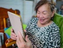 非常愉快的老亚裔妇女看片剂在她的房子,老c里 图库摄影