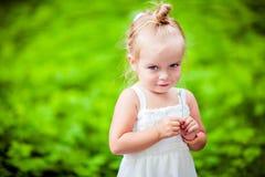 非常拿着花的一件白色礼服的逗人喜爱的矮小的白肤金发的女孩我 免版税库存图片