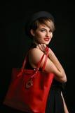 非常拿着fansy红色袋子的时髦的女人在照相机喜欢微笑和摆在 免版税库存照片