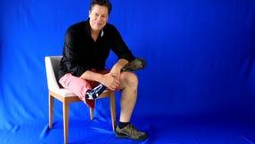 非常有同情心的人在椅子输入并且坐,招呼并且使用与假肢 影视素材