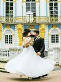 非常有拥抱和跳舞在蓝色宫殿,生活方式人概念的新郎的美丽的新娘 图库摄影