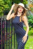 非常有红色嘴唇的性感的女孩在有站立在外部附近的圆点的帽子礼服在公园在一个晴朗的夏日 免版税图库摄影