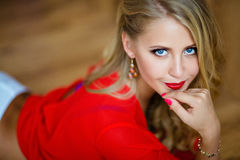 非常有蓝眼睛的美丽的性感的白肤金发的女孩在红色女衬衫 免版税库存照片