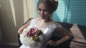 非常有蓝眼睛的美丽的金发碧眼的女人在一个窗口附近的一件白色新娘礼服与花花束  影视素材