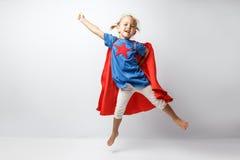 非常激动的小女孩穿戴了象跳沿着白色墙壁的超级英雄 库存图片