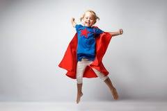 非常激动的小女孩穿戴了象跳沿着白色墙壁的超级英雄 免版税图库摄影