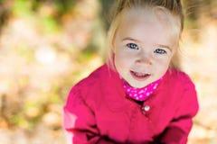 非常红色夹克的逗人喜爱的白肤金发的女孩 免版税库存图片