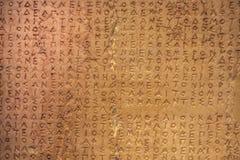 非常织地不很细老损坏的希腊文字被雕刻入与镇压的一块石头和损伤和色变-粒状区域在哪里损坏了 免版税图库摄影
