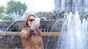 非常美丽和尼斯女孩在喷泉附近做一selfie 影视素材