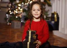 非常美好的长发女孩微笑和拿着在新的一件礼物 库存图片