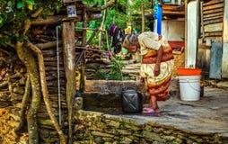 非常老弯成拱状的妇女用水填装一个五加仑装之汽油罐 库存图片