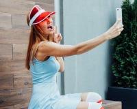 非常获得乐趣和摆在为户外社会网络的selfie的性感的红头发人秀丽女孩在一个温暖的夏天晚上在蓝色tren 免版税库存图片
