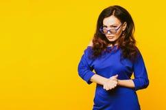 非常蓝色衣服的恼怒的成熟看对照相机的女实业家和玻璃 免版税库存照片