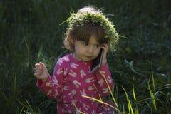 非常逗人喜爱的女孩坐绿草和谈话在智能手机 库存照片