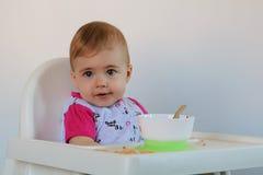非常逗人喜爱的小女孩坐儿童的椅子 免版税库存照片