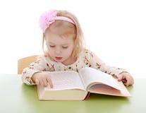 非常读一本厚实的书的聪明的小女孩 免版税图库摄影