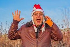 非常滑稽的圣诞老人帽子的情感人谈话在电话 免版税图库摄影
