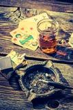 非法啤牌的老桌用伏特加酒、香烟和卡片 免版税图库摄影