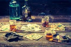 非法啤牌的葡萄酒桌用伏特加酒、香烟和卡片 免版税库存照片