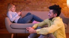 非洲人坐演奏与控制杆的计算机游戏和白种人女孩与在沙发的智能手机一起使用的地板在舒适家 股票视频
