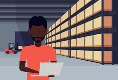 非洲使用膝上型计算机小包箱子的人铲车装载者运作的仓库内部在机架后勤交付货物服务 皇族释放例证