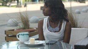 非洲女性自由职业者画象看起来疲乏和乏味,饮用的咖啡和使用智能手机的自助食堂的 免版税库存图片