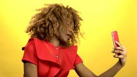 非洲妇女在他的手上拿着一个电话并且做selfie 黄色背景 股票视频