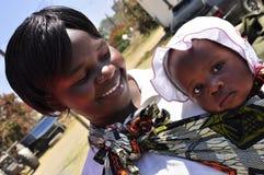 非洲婴孩逗人喜爱的现代妇女 库存照片
