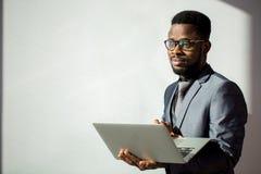 非洲工友佩带的玻璃和使用膝上型计算机在办公室 库存照片