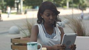 非洲年轻女商人工作和使用片剂在室外咖啡馆 库存图片