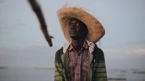 非洲渔夫画象草帽的 年轻人坐在小船的和抓住单独钓鱼 影视素材