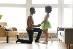 非洲父亲开始认真对待一个膝盖举行女儿手 库存照片