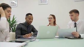 非洲经理提出他的报告的结果给他的同事在共同工作的屋子里 影视素材
