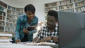 非洲聊天和笑在准备时的女孩和人对检查在学生图书馆里 影视素材