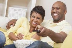 非洲裔美国人的夫妇注意的电视 免版税库存图片