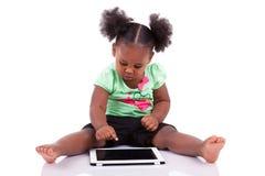 非洲裔美国人的女孩少许个人计算机片剂使用 免版税库存图片