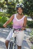非洲裔美国人的妇女骑马自行车 免版税库存照片