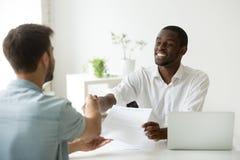 非洲雇主握手新的聘用白种人雇员藏品 免版税库存照片