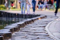 非焦点或被弄脏的照片与走沿被铺的边路的人在公园 图库摄影