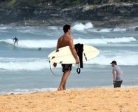 非职业冲浪者在与他的冲浪板的海滩走 免版税图库摄影