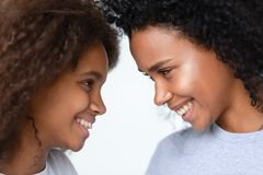 非裔美国人的享受片刻的母亲和青少年的女儿的关闭 免版税图库摄影