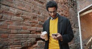 非裔美国人的使用室外的智能手机的学生饮用的咖啡的慢动作 影视素材