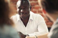 非裔美国人的商业领袖的图象在工作环境里的看照相机 免版税库存照片