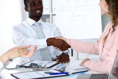 非裔美国人的商人与女性伙伴握手在办公室 免版税库存照片
