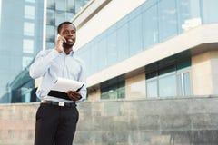 非裔美国人的商人与纸一起使用户外 免版税图库摄影