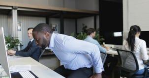 非裔美国人的商人在得到以后在自行车工作进入办公室坐下到现代露天场所的工作场所 股票录像