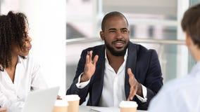 非裔美国人的商人教练谈判员讲话在不同的队会议上 免版税库存图片