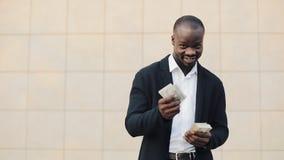 非裔美国人的商人画象在计数金钱身分的衣服的在办公室中心附近 庆祝他的他 股票录像