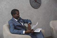 非裔美国人的商人读书报纸和检查时间 免版税库存图片